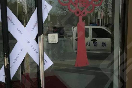 雄县一处售楼处门前停着城管车辆,车上的大喇叭循环播放禁止炒房的内容